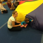 Livy is shy to go under the parachute without mom