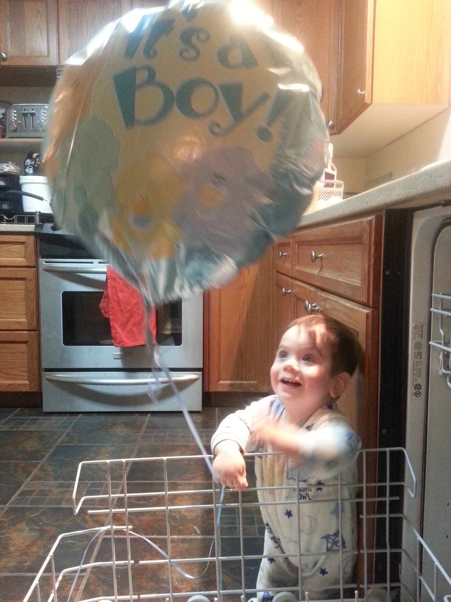 "Landen with an old ""baby shower"" baloon"